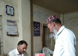 Dairy farmers withdrawing money from Amul Micro ATM